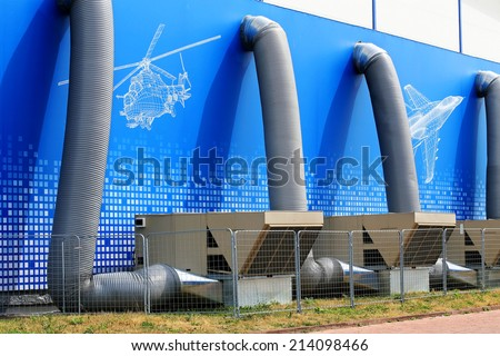 Ventilation pipes and actuators on the roof of an industrial building - stock photo