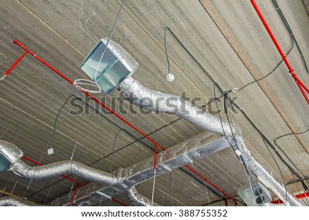 Ventilation pipes in silver insulation material hanging from the ceiling inside new building. - stock photo