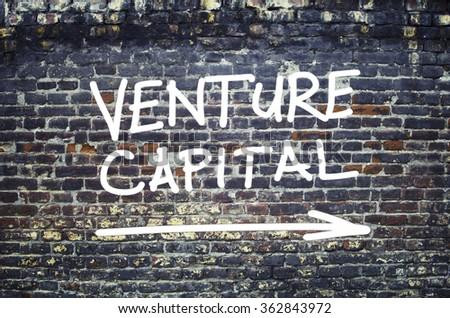 Venture Capital text on brick wall - stock photo