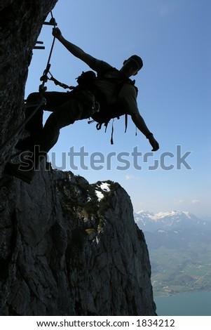 Venturous sport - silhouette of a climber - stock photo