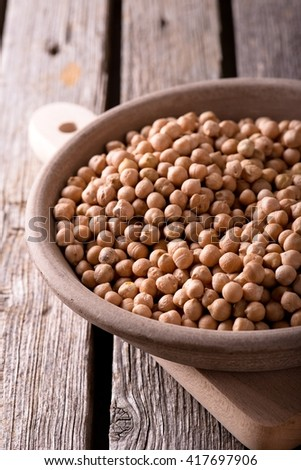 Verical photo. Yellow dry chickpeas. Chickpeas in clay bowl. Earthen plate with legumes. Bowl on chopping board. Bowl on old wooden board. Old worn wooden board with grey color. - stock photo