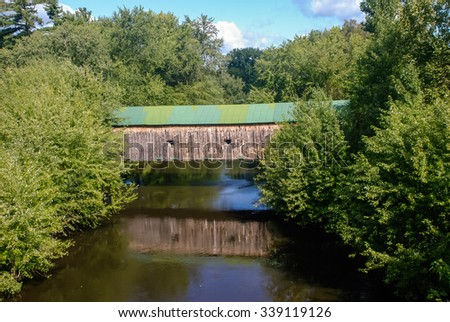 Vermont Covered Bridges.  Hammond Covered Bridge, built in 1842. Pittsford Vermont.  Reflecting in calm river. - stock photo
