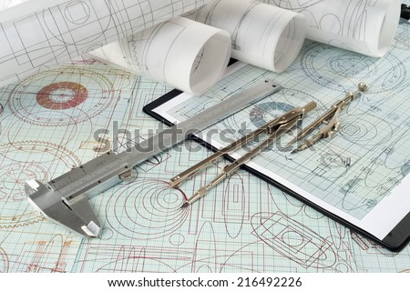 vernier callipers , compasses, clipboard and drawings, selective focus