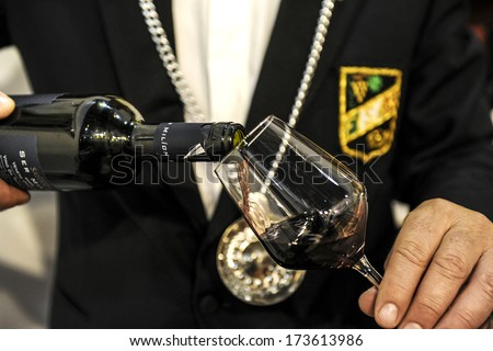 VERONA ITALY - APRIL 08: Sommelier pouring a red glass of wine during Vinitaly, International Wine Fair in Verona, April 08, 2010.