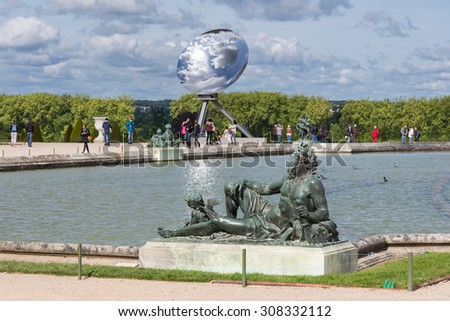 VERSAILLES PARIS, FRANCE - MAY 30: Visitors in garden Palace Versailles with statue and pond on May 30, 2015 at the Palais of Versailles near Paris, France - stock photo