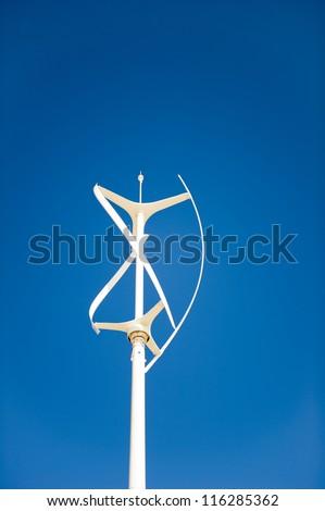 Vertical axis wind turbine against a clear deep blue sky - stock photo