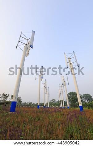 vertical axis wind turbine under blue sky - stock photo