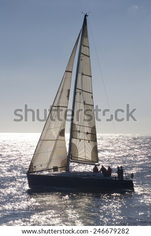 Vertical back-lighting view of a sailboat on the sea . Sailboat. - stock photo