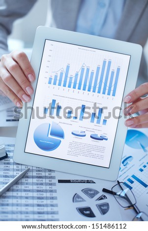 Vertical close-up image of a businesswoman holding a digital tablet with financial data on the screen