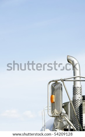 Vertical close-up of a truck's mirrors and exhaust pipe against the sky giving copy space, contrast of bright blue sky and pollution source - environmental concept. - stock photo