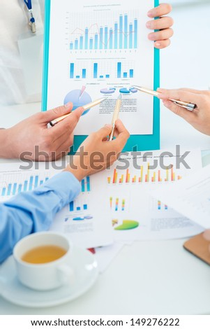 Vertical close-up of business people pointing at the statistical document - stock photo