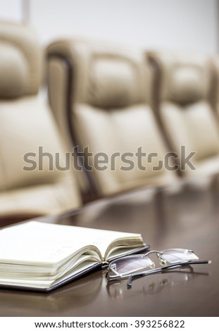 Vertical closeup of notepad an glasses on table in empty corporate conference room before business meeting in office  - stock photo