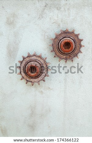 Vertical closeup of two rusty gears on dirty wall with copy space - stock photo
