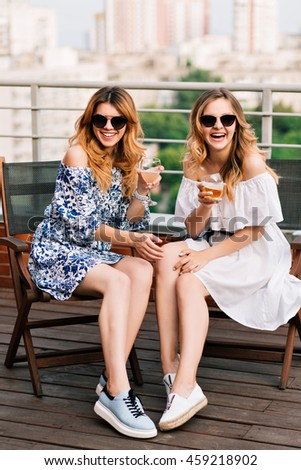 Vertical full-lengh photo of two attractive fair-haired girls  sitting at table  on terrace on city background. They wear dresses , sunglasses. They are smiling to the camera.