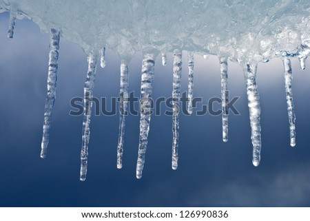 Vertical icicles flowing down from an ice floe. - stock photo