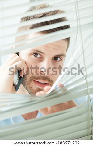 Vertical image of a businessman peeping through blinds while talking by phone