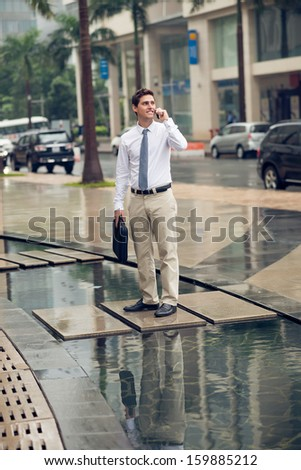 Vertical image of a businessman talking by the phone with a bag in hands standing outside - stock photo