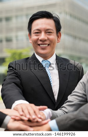 Vertical image of a businessman with his colleagues'?? hands on the foreground - stock photo