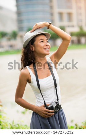 Vertical image of a carefree beauty with a camera enjoying summer in the city - stock photo