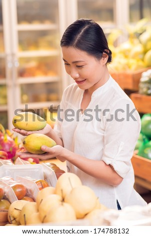 Vertical image of a customer choosing mango fruit in the grocery  - stock photo