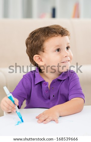 Vertical image of a funny little boy painting something on the paper at home  - stock photo