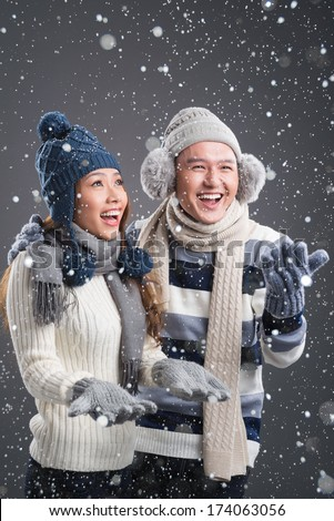 Vertical image of a funny winter couple having fun with snow  - stock photo