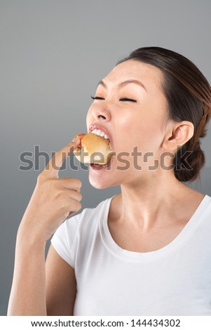 Vertical image of a greedy young woman eating a hot dog to the very last bit of it - stock photo