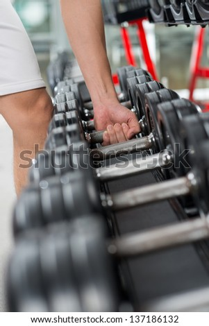 Vertical image of a male athlete taking a dumbbell from a row - stock photo