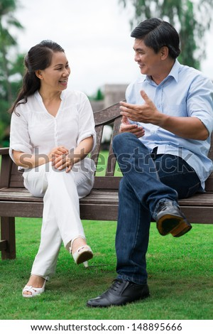 Vertical image of a mature couple sitting on the bench and talking outside - stock photo