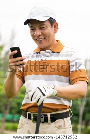Vertical image of a mature golf player standing with his smartphone during the break - stock photo