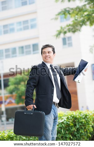 Vertical image of a modern businessman with a handbag standing outside