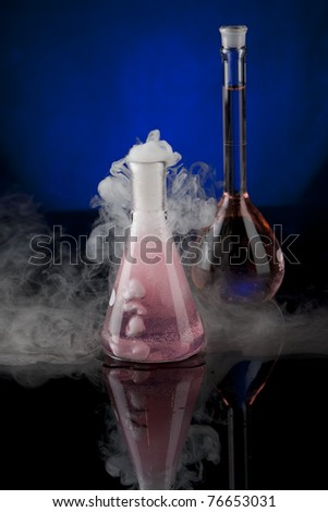Vertical image of a pair of flasks, one with a red liquid, another with a bubbling pink liquid on a black reflective surface with a blue background. - stock photo