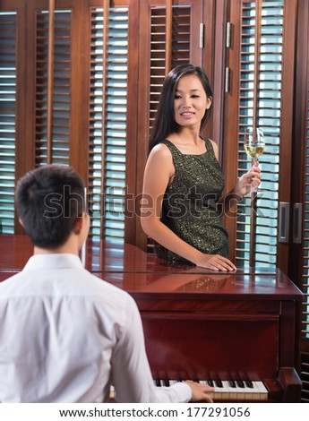 Vertical image of a pianist playing for a beautiful lady standing with a glass of white wine on the foreground