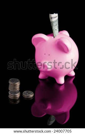 "Vertical image of a piggy bank ""looking"" at a stack of quarters with a dollar bill in it's slot. - stock photo"