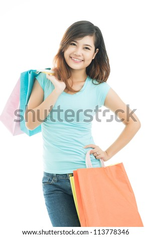 Vertical image of a pleasant young woman with friendly smile doing shopping - stock photo