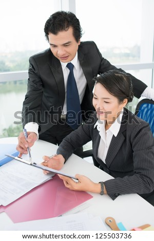 Vertical image of a pretty female intern working under the guidance of her boss - stock photo