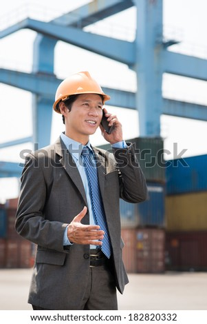 Vertical image of a smiley port worker talking by phone in industry area  - stock photo