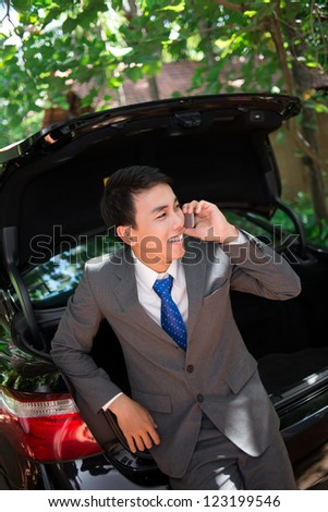 Vertical image of a successful businessman leaning onto his car and negotiating on the mobile phone - stock photo