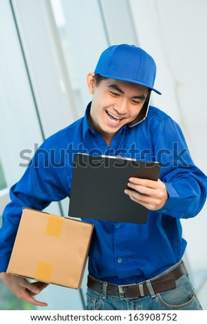 Vertical image of a young courier at work  - stock photo