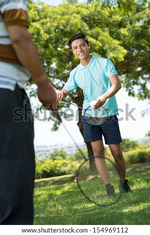 Vertical image of a young grandson playing badminton with his grandfather on the foreground - stock photo