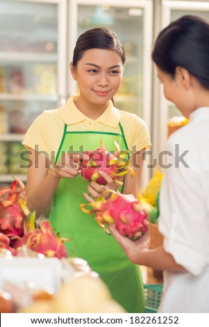 Vertical image of a young saleswoman advising a customer to buy the ripe dragon fruit on the foreground  - stock photo