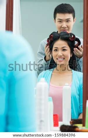 Vertical image of a young woman having hair styling on the foreground - stock photo