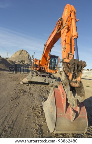 Vertical image of an excavator (aka rubber duck or digger) in front of a large heap of asphalt. - stock photo