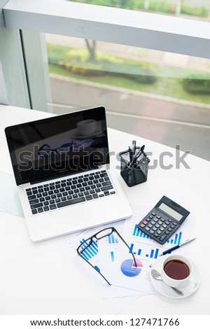 Vertical image of an office desk with a laptop, stationary and financial reports - stock photo