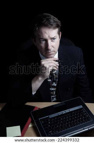 Vertical image of business man, looking at computer screen while holding pen, working late with black background  - stock photo