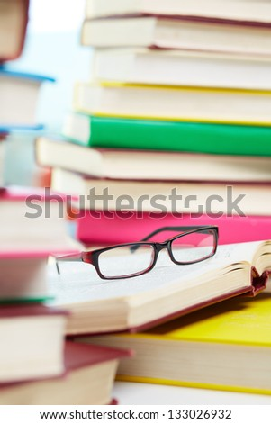 Vertical image of eyeglasses lying over opened book in the library - stock photo