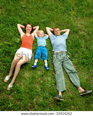 Vertical image of family resting on the grass - stock photo