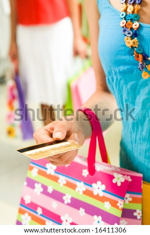 Vertical image of female hand with plastic card giving it to shop assistant - stock photo