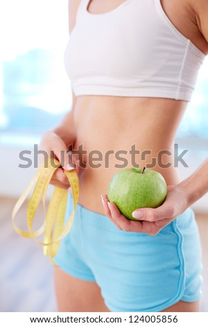Vertical image of fit female holding green apple in hand - stock photo