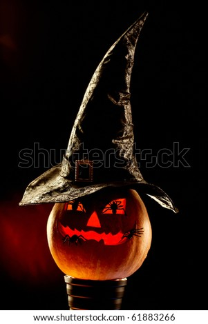 Vertical image of Halloween grinning pumpkin with hat and spiders - stock photo